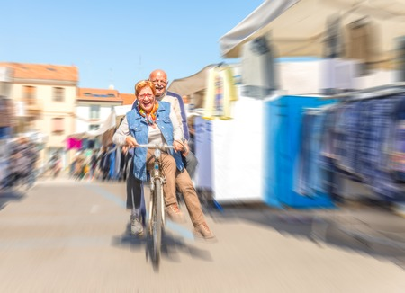 couple having fun: Senior couple riding on bicycle outdoors - Playful man and woman in the age of 60s having fun while sharing the same bike on the streets - Radial blur motion effect Stock Photo