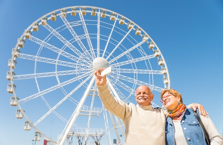 taking a wife: Senior couple taking a selfie at amusement park - Two persons in the 60s having fun with new technologies outdoor - Husband taking a photograph with his wife on vacation Stock Photo