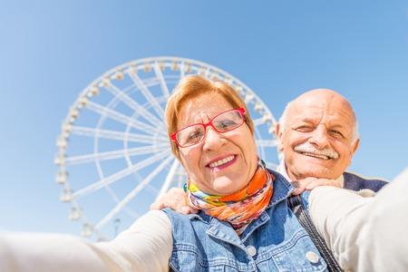 damas antiguas: Matrimonios de edad tomando una selfie en el parque de diversiones - Dos personas en la d�cada de los 60 que se divierten con las nuevas tecnolog�as al aire libre Foto de archivo