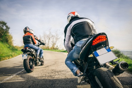 Two motorbikes driving in the nature - Friends driving racing motorcycles with their girlfriends Foto de archivo