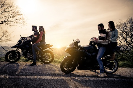 Two motorbikes driving in the nature - Friends driving racing motorcycles with their girlfriends - Group of bikers stop in a panoramic view point and look at suggestive sunset Foto de archivo