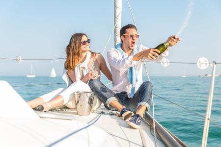 Pareja celebra aniversario con champán en un barco - Atractivo hombre caucásico descorchar champán y tener fiesta con su novia de vacaciones - Dos turistas jóvenes que se divierten en un paseo en barco en el verano