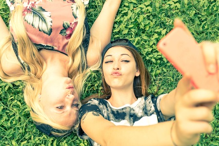 best friends: Two pretty girls taking a self portrait - Young women with a sportive casual outfit lying on meadow and having fun while taking a selfie