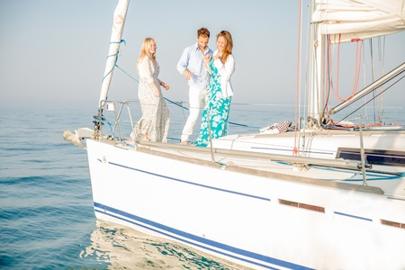 boat party: Group of young people partying and dancing on a sailing boat - Two beautiful women and attractive man having fun on a boat while on vacation - Rich people enjoying party