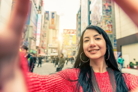 Beautiful woman making a frame with fingers in front of face - Brunette girl taking a picture in Akihabara,Tokyo Stock Photo