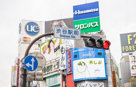 scramble: TOKYO, JAPAN - FEBRUARY 10,2015: Street signs and billboards at Shibuya Crossing,Tokyo. The scramble crosswalk is one of the largest in the world.