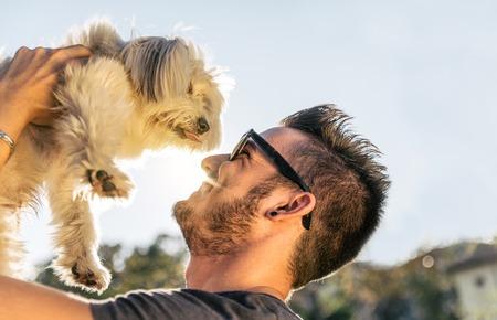 dog days: Perro y su dueño - Enfriar perro y hombre joven que se divierte en un parque - conceptos de amistad, animales domésticos, unidad Foto de archivo