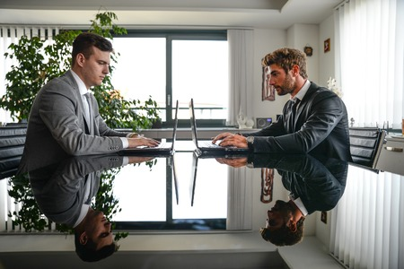 lawer: Business men working on computer desk - Busy office workers computing on lap top - Two men sitting at computer desk in front of each others Stock Photo