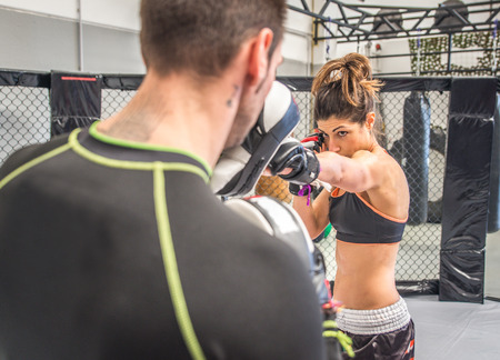 martial arts woman: mma training with focus mitt Stock Photo