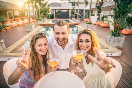 Friends at party drinking cocktails and having fun - Three tourists drinking aperitif in a tropical luxurious restaurant