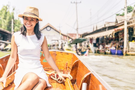 floating market: Beautiful asian woman visiting the Floating Market in Bangkok on a boat tour - Asian tourist smiling and looking at camera on a typical thai boat Stock Photo