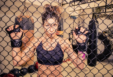 self  discipline: Martial arts fighter looking straight at camera from the cage - Determinated athletic woman in a fighting cage Stock Photo