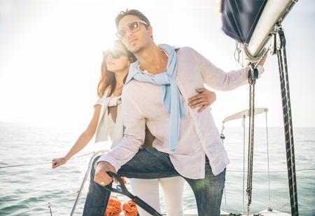 보트 항해 연인의 아름다운 커플 - 젊은 매력적인 남자 요트의 키를 잡고 멀리 찾고 - 두 패션 모델 일몰 세일링 보트에 포즈