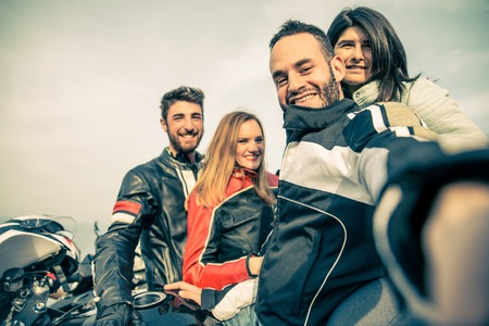 jinete: Los ciclistas que toman selfie con c�mara - Cuatro amigos sonriendo de conducci�n de motocicletas de carreras con sus novias - Dos parejas felices se detienen en un punto de vista panor�mica y se fotograf�an