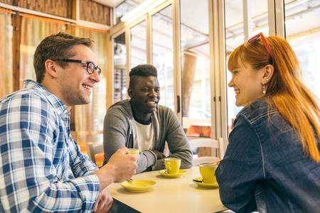 mejores amigas: Amigos que hablan y que sonríen en un café - Grupo de estudiantes multirraciales jóvenes reunidos en un bar y beber café - personas alegres felices en un restaurante