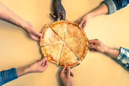 are taking: Six friends sharing a pizza in a restaurant - Hands taking a pizza margherita slice - Concepts about food,nutrition,party and friendship
