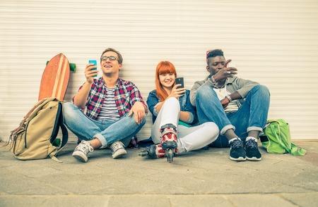 路上で座っていると見ている携帯電話 - 新技術を楽しんで若い現代流行に敏感な人々 - 民族グループ技術への依存症を表す別の民族の友人のグルー