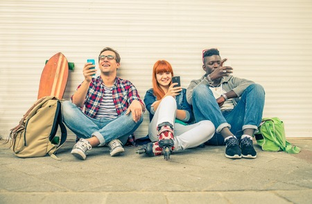 technology: Gruppo di amici di varie etnie che si siedono in strada e guardando cellulare - Giovani a vita bassa moderna divertirsi con le nuove tecnologie - gruppo multietnico che rappresenta la dipendenza da tecnologie Archivio Fotografico