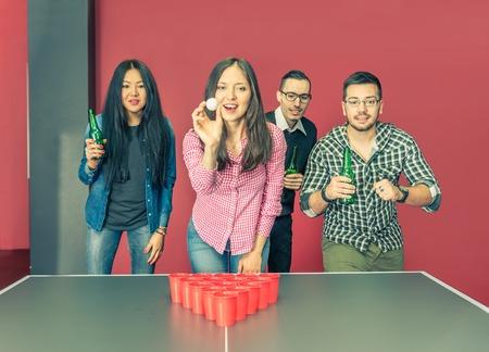 hombre tomando cerveza: Cuatro jóvenes estudiantes universitarios a jugar en la cerveza pong en un hostal - Grupo de amigos multirraciales beber cerveza y -conceptos divertidas sobre la juventud, fiesta y reunión social Foto de archivo