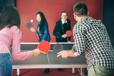 jugando tenis: Dos parejas de jóvenes jugando al ping pong en un hostal - Cuatro estudiantes con paletas de ping pong que se divierte en un pub