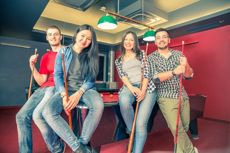pool table: Two couples having fun at billiard - Group of multiracial young people standing next to pool table and holding cue - Students spending an evening at pub