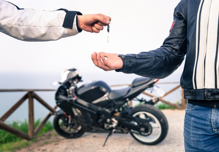 key exchange. Motorcycle concept. friends exchanging the bike key.