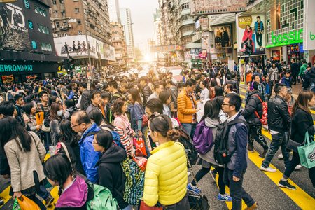 HONG KONG - FEBRUARY 12,2015: people crossing Nathan Road. Hong Kong is well known for the myriad of neon lights located above the roadways.Tilted horizon. Editorial
