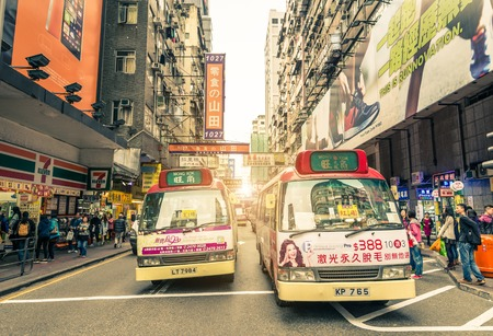 is well known: HONG KONG - FEBRUARY 12,2015: mini van buses in Mong Kok. Hong Kong is well known for the myriad of neon lights located above the roadways.