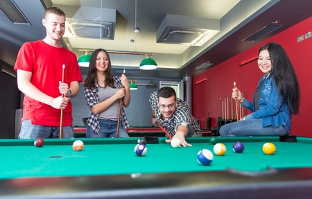 snooker room: pool game. group of friends playing pool together. concept about fun, friendship,leisure and people