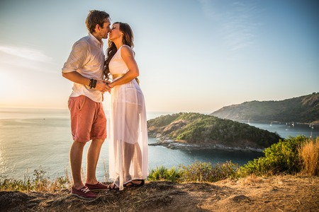 romantic date: Couple in love kissing at sunset with panoramic landscape in the background - Lovers on a romantic date outdoors holding hands and flirting Stock Photo