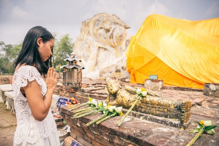 Asian woman praying at Buddha  temple in Ayutthaya, Thailand - Young beautiful thailandese girl with linked hand in sign of respect to religious statue photo