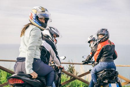 Twee motoren rijden in de natuur - Vrienden rijden race motoren met hun vriendinnen - Groep van fietsers stoppen in een panoramisch uitzicht punt en kijk naar suggestieve zonsondergang Redactioneel
