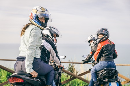 Two motorbikes driving in the nature - Friends driving racing motorcycles with their girlfriends - Group of bikers stop in a panoramic view point and look at suggestive sunset Editorial
