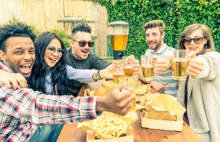 Group of mult-ethnic friends toasting beer glasses - Happy people partying and eating in home garden - Young active adults in a picnic area with burgers and drinks Standard-Bild