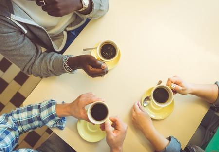 personas platicando: pausa para el café. tres amigos sentados y tienen un café en una tienda. concepto sobre la gente, café y bares