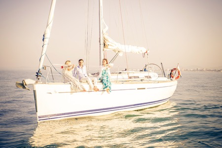 Group of young people sitting on a sailing boat - Two beautiful women and attractive man having fun on a boat while on vacation - Rich people enjoying party