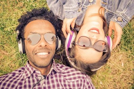 草原に横たわって、トレンディなイヤホン - アフロ アメリカ人の男と白人女性の肖像画で音楽を聴く人のカップル