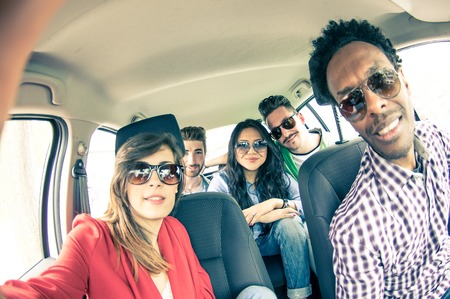 Group of five people driving to vacation and taking a selfie in the car - Happy people of of diverse ethnics in an automobile - Frinds renting a car and driving somewhere