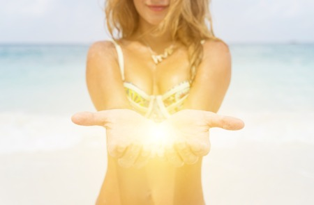 light in the palm of the hands. beautiful blurred girl open the hands and reveals light in between photo