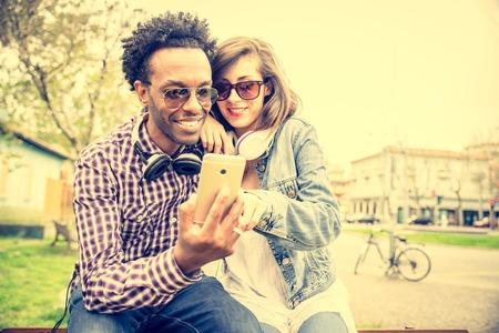 amantes: Pareja de amantes multirraciales mira smartphone y de fondo urbano - chico afroamericano Stilish y bella mujer viendo algo divertido en la pantalla del teléfono Foto de archivo