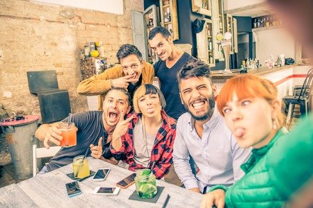 students fun: Group of friends having fun in a cocktail bar and taking a selfie - Young students partying together and taking picture - Concepts about fun,youth,technologies and nightlife Stock Photo