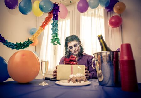 madhouse: madness party. sad clown sitting alone at his birthday party