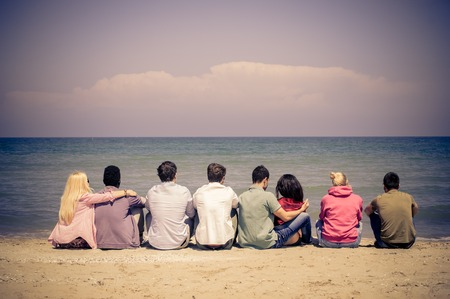 multi racial group: Group of mutiracial friends sitting on the beach and looking at horizon - Young students on a summer vacation