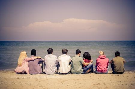 racismo: Grupo de amigos Mutiracial sentados en la playa y mirando el horizonte - Jóvenes estudiantes en vacaciones de verano