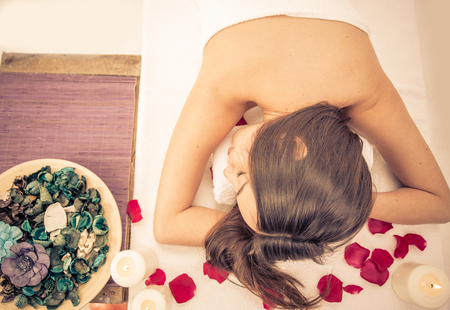 relaxing at the spa. asian woman lying down in the massage saloon photo