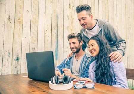 juventud: Grupo de gente inconformista j�venes que trabajan con ordenador port�til - Los estudiantes universitarios reunidos en un lugar conectado inal�mbrico para trabajar con las nuevas tecnolog�as - conceptos de negocio y tecnolog�as de inicio Foto de archivo