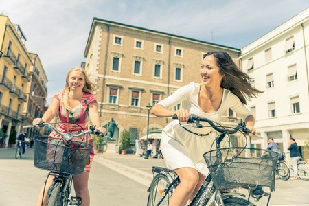 two women: Happy couple riding bikes in the city - Two girlfriends on bikes talking and laughing - Best friends spending time together on vacation Stock Photo