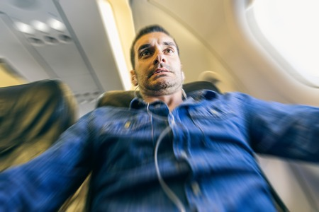 Airplane passenger in shock while the plane is in a turbolence area photo