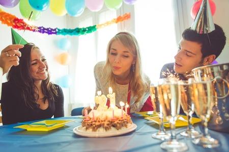 gente celebrando: fiesta de cumplea�os en casa. tres amigos celebrando el cumplea�os de la muchacha con fiesta sorpresa en casa. concepto sobre el cumplea�os, fiesta y la gente