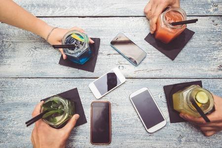 saúde: amigos com cocktails. Quatro mãos segurando coquetéis. Telefones inteligentes estão em cima da mesa. tendo um intervalo de tecnologia e curtindo a vida